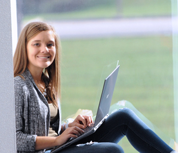 Student with laptop sitting in large window